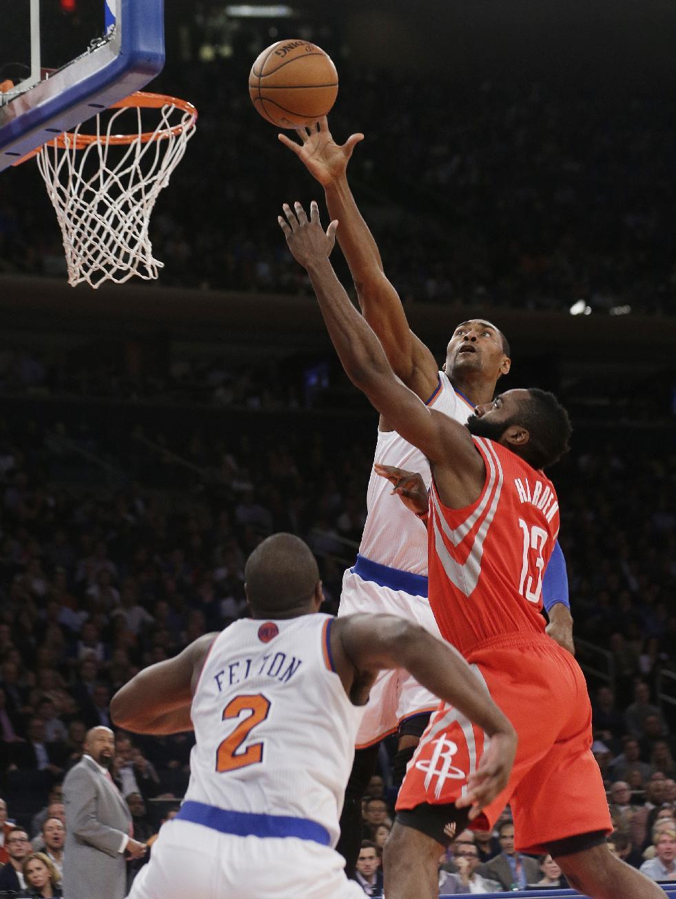 New York Knicks' Metta World Peace blocks a shot by Houston Rockets' James Harden, right, as Knicks' Raymond Felton, left, defends during the second half of an NBA basketball game Thursday, Nov. 14, 2013, in New York. The Rockets won 109-106