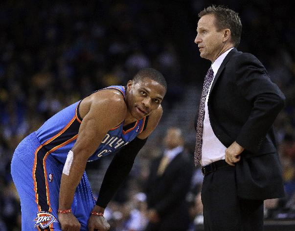 Oklahoma City Thunder coach Scott Brooks, right, speaks with Russell Westbrook during the first half of an NBA basketball game against the Golden State Warriors, Thursday, Nov. 14, 2013, in Oakland, Calif