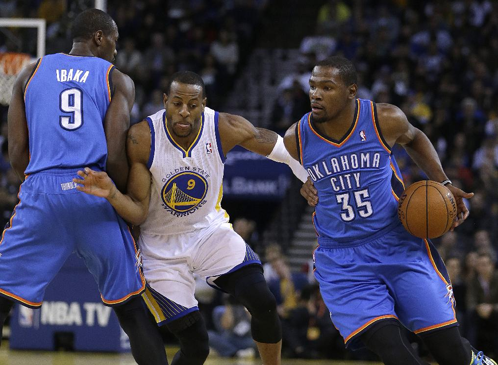 Oklahoma City Thunder's Kevin Durant, right, drives the ball around Golden State Warriors' Andre Iguodala, center, as Serge Ibaka sets a pick during the first half of an NBA basketball game Thursday, Nov. 14, 2013, in Oakland, Calif