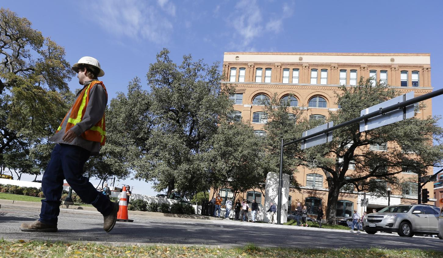 A worker walks by a work cone marking off a section of street surface that was ripped up near the Sixth Floor Museum, in the background, on Dealey Plaza where JFK was assassinated in downtown Dallas,  Tuesday, Nov. 19, 2013. Days before Dallas' observance of JFK assassination date, 'X's marking shooting spots on the street were removed by city work crews as the city prepares for Friday's events that will solemnly commemorate the 50th anniversary of JFK being assassinated
