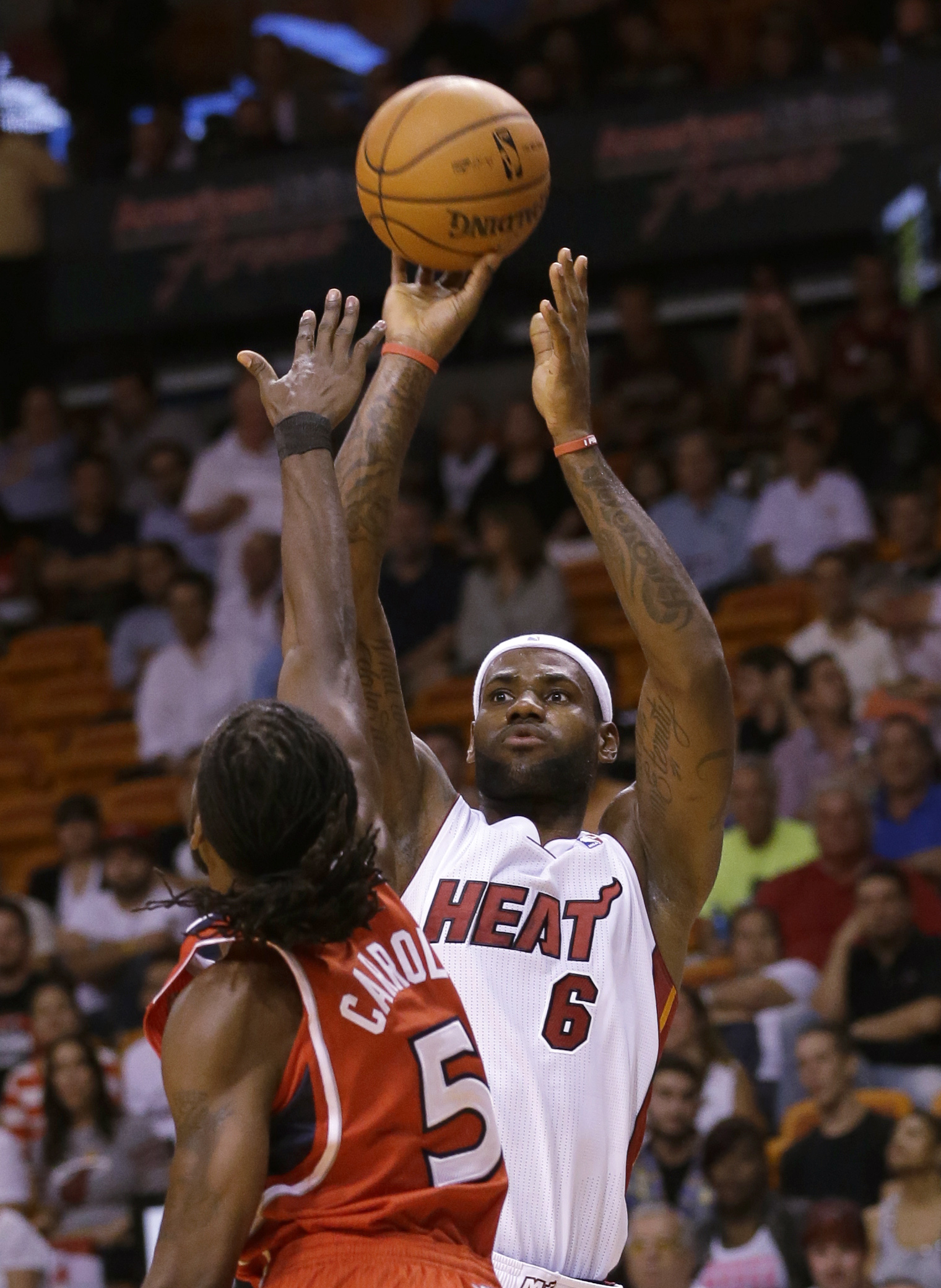 Miami Heat forward LeBron James (6) goes up for a shot against Atlanta Hawks forward DeMarre Carroll (5) during the first half of an NBA basketball game, Tuesday, Nov. 19, 2013 in Miami