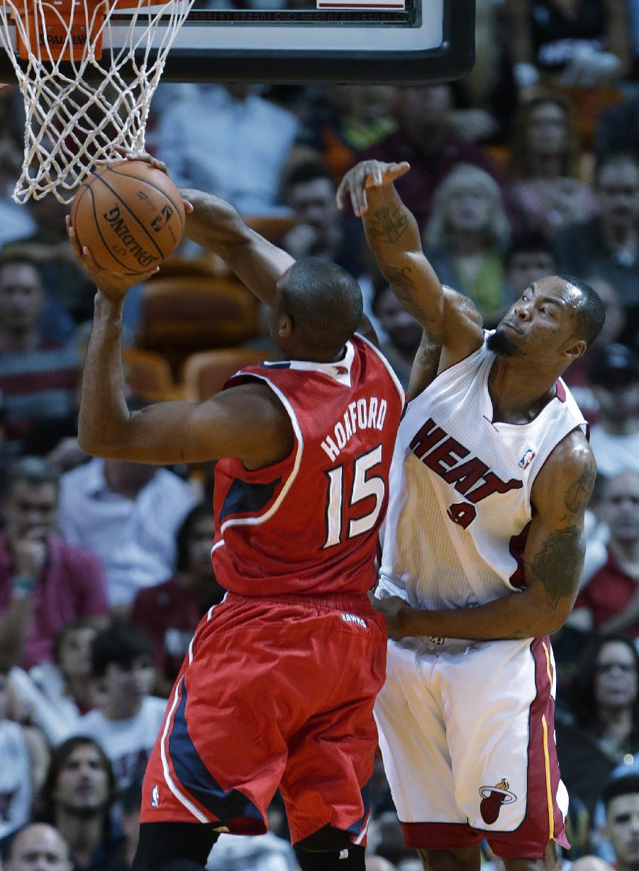 Atlanta Hawks center Al Horford (15) of the Dominican Republic, goes up for a shot against Miami Heat forward Rashard Lewis (9) during the first half of an NBA basketball game, Tuesday, Nov. 19, 2013 in Miami