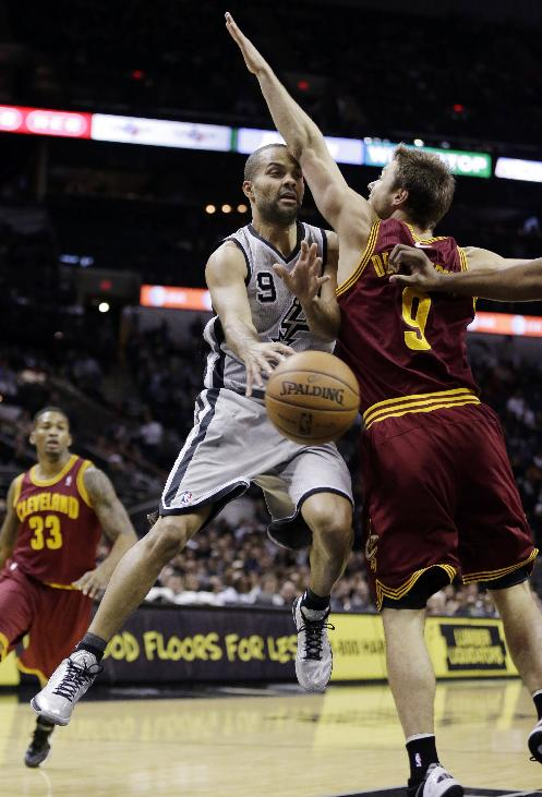 San Antonio Spurs' Tony Parker (9), of France, passes the ball around Cleveland Cavaliers' Matthew Dellavedova, right, during the first half of an NBA basketball game Saturday, Nov. 23, 2013, in San Antonio