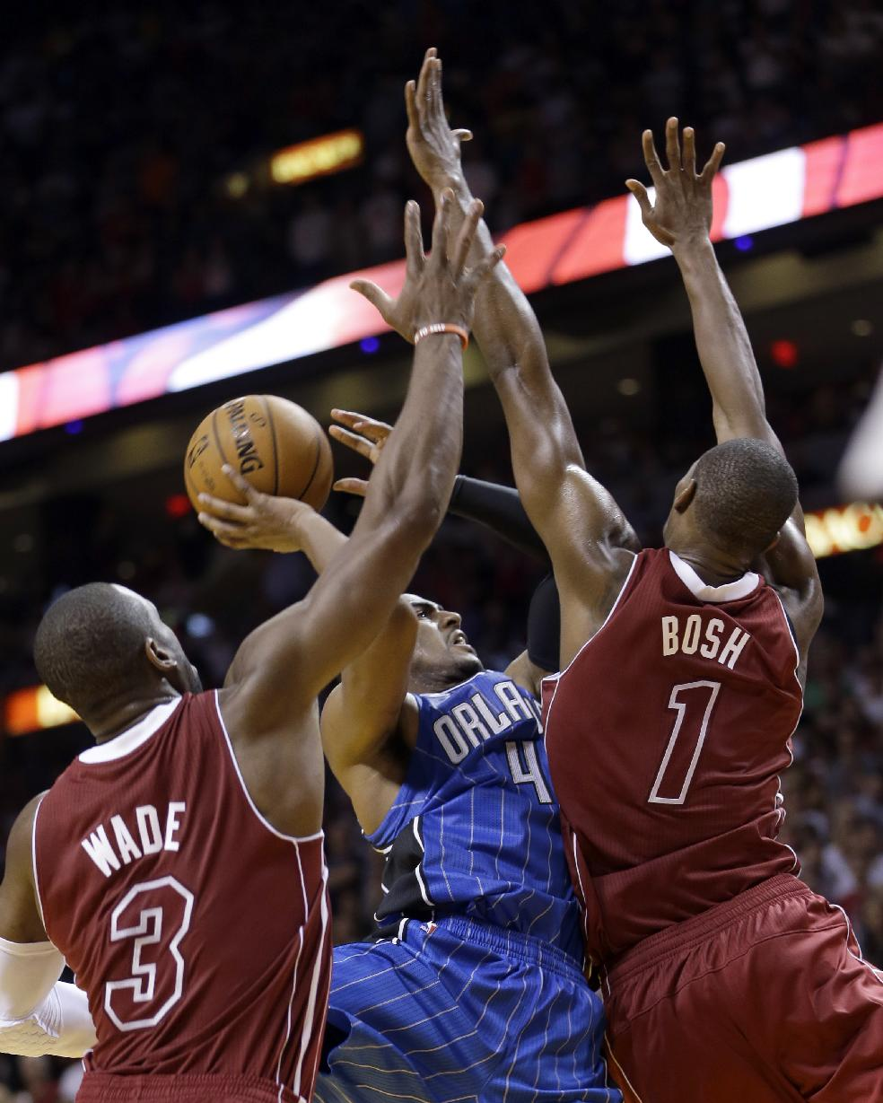 Miami Heat center Chris Bosh (1) and Dwyane Wade (3) apply pressure on Orlando Magic shooting guard Arron Afflalo (4) as he prepares to shoot in the fourth quarter of an NBA basketball game, Saturday, Nov. 23, 2013, in Miami. The Heat won 101-99