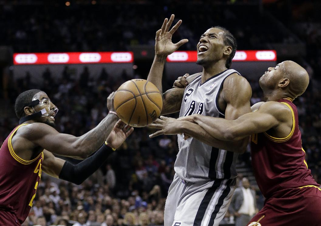 San Antonio Spurs' Kawhi Leonard, center, is fouled by Cleveland Cavaliers' Jarrett Jack, left, as Kyrie Irving, right, helps defend the play during the first half of an NBA basketball game Saturday, Nov. 23, 2013, in San Antonio