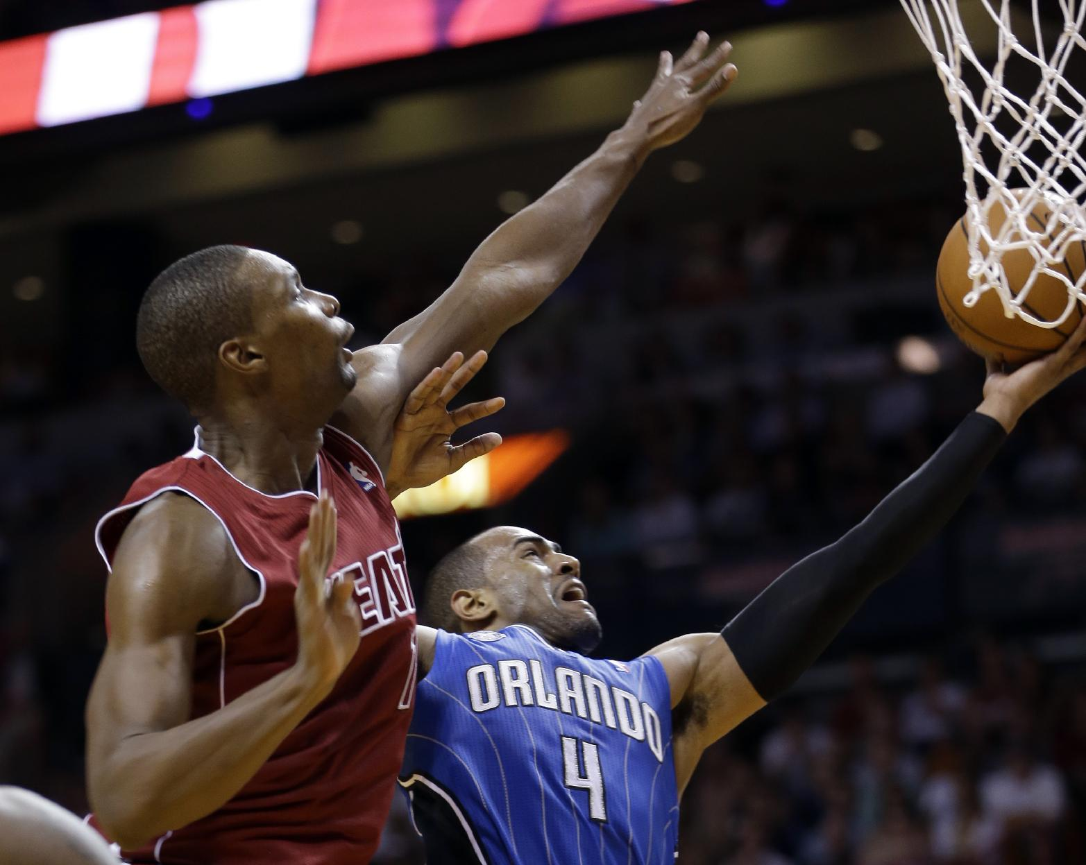 Orlando Magic shooting guard Arron Afflalo (4) goes up to the basket against Miami Heat center Chris Bosh (1) in the fourth quarter of an NBA basketball game, Saturday, Nov. 23, 2013, in Miami. The Heat won 101-99