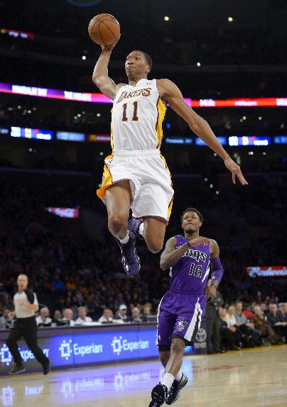 Los Angeles Lakers guard Wesley Johnson, left, goes up for a dunk as Sacramento Kings guard Ben McLemore stands by during the first half of an NBA basketball game Sunday, Nov. 24, 2013, in Los Angeles