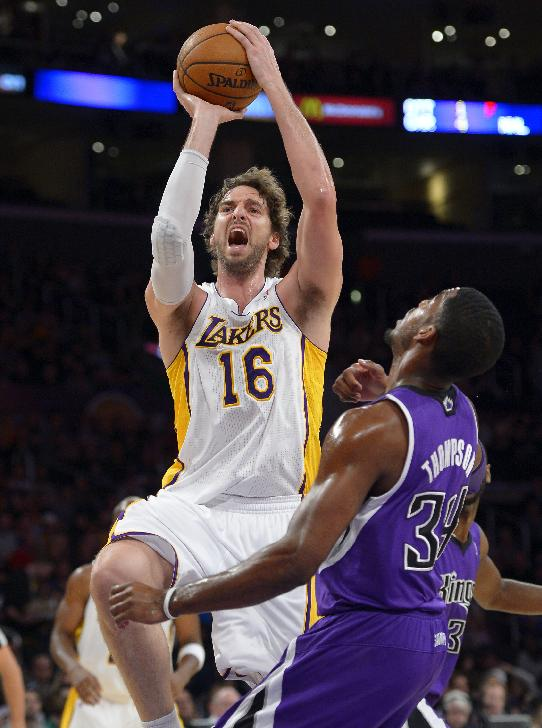 Los Angeles Lakers center Pau Gasol, left, of Spain, puts up a shot as Sacramento Kings forward Jason Thompson defends during the first half of an NBA basketball game Sunday, Nov. 24, 2013, in Los Angeles