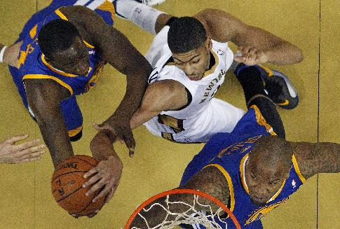 New Orleans Pelicans power forward Anthony Davis, center, battles for a rebound between Golden State Warriors small forward Draymond Green, top left, and power forward Marreese Speights in the second half of an NBA basketball game in New Orleans, Tuesday, Nov. 26, 2013. The Warriors won 102-101