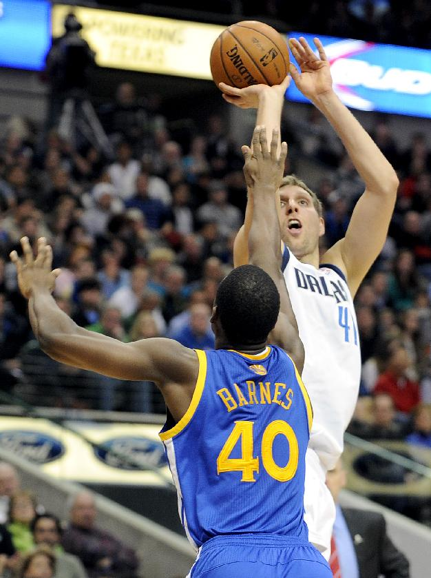 Dallas Mavericks power forward Dirk Nowitzki (41) shoots over Golden State Warriors small forward Harrison Barnes (40) in the first half during an NBA basketball game on Wednesday, Nov. 27, 2013 in Dallas