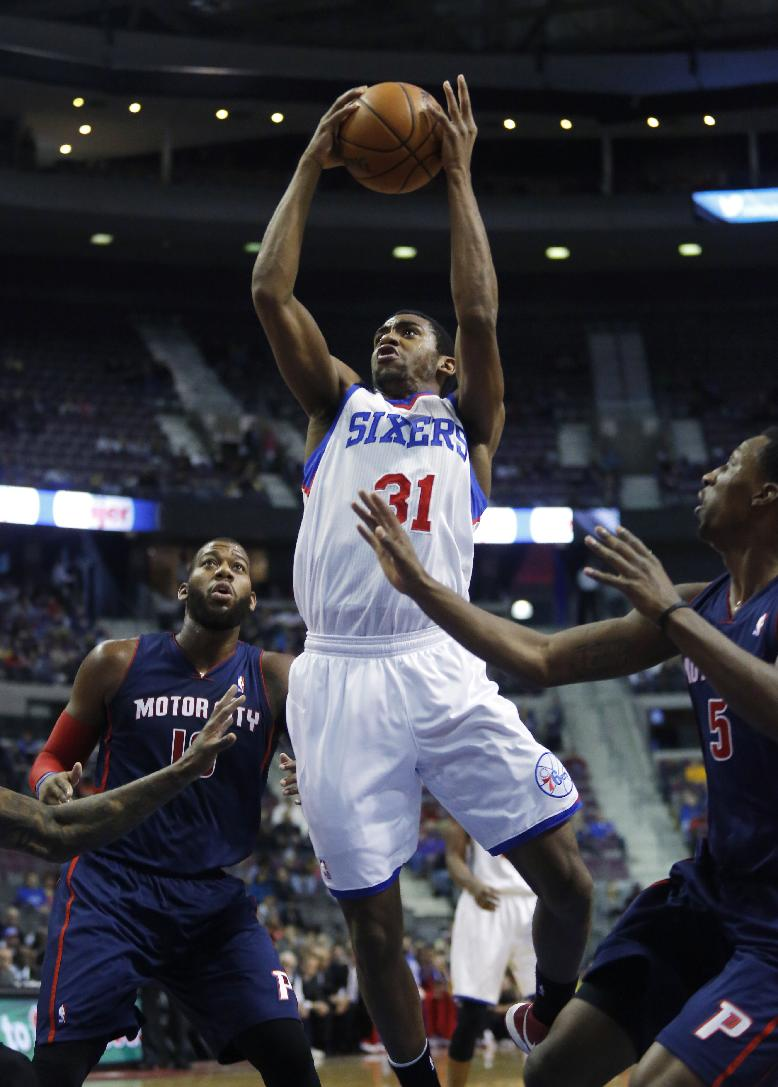 Philadelphia 76ers forward Hollis Thompson (31) shoots between Detroit Pistons center Greg Monroe (10) and guard Kentavious Caldwell-Pope (5) during the first half of an NBA basketball game on Sunday, Dec. 1, 2013, in Auburn Hills, Mich
