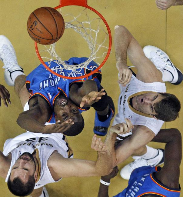 Oklahoma City Thunder power forward Serge Ibaka, center battles under the rim with New Orleans Pelicans power forward Ryan Anderson (33), bottom left, and center Jeff Withey, right, in the first half of an NBA basketball game in New Orleans, Friday, Dec. 6, 2013