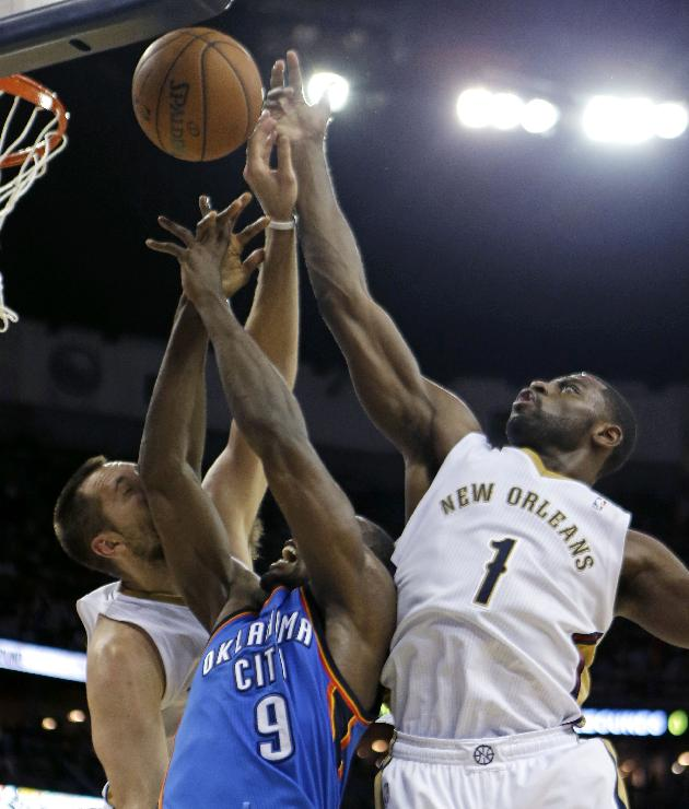 Oklahoma City Thunder power forward Serge Ibaka (9) battles for a rebound with New Orleans Pelicans point guard Tyreke Evans (1) and power forward Ryan Anderson in the first half of an NBA basketball game in New Orleans, Friday, Dec. 6, 2013