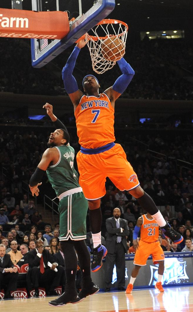 New York Knicks' Carmelo Anthony (7) dunks a basket over Boston Celtics' Jared Sullinger (7) during the first half of an NBA basketball game on Sunday, Dec. 8, 2013, in New York. The Celtics won 114-73