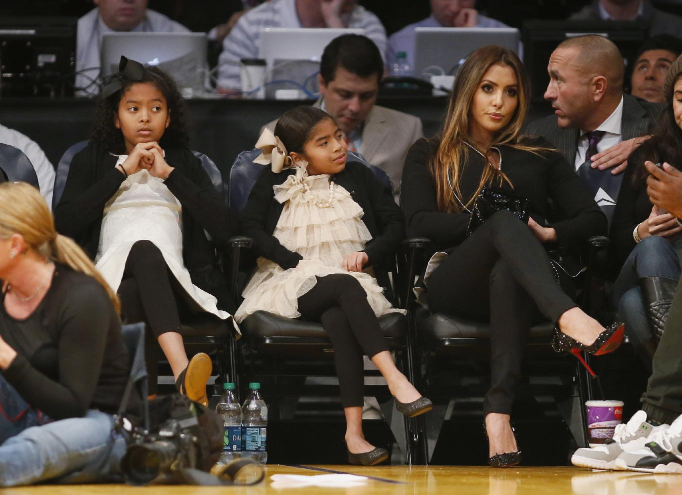 Vanessa Bryant, right, wife of Los Angeles Lakers' Kobe Bryant, sits with their daughters Natalia Diamante Bryant, left, and Gianna Maria-Onore Bryant, center, as the Lakers play the Toronto Raptors in an NBA basketball game in Los Angeles, Sunday, Dec. 8, 2013