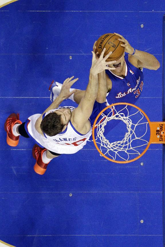 Los Angeles Clippers' Blake Griffin, right, goes up for a shot against Philadelphia 76ers' Spencer Hawes during the first half of an NBA basketball game, Monday, Dec. 9, 2013, in Philadelphia