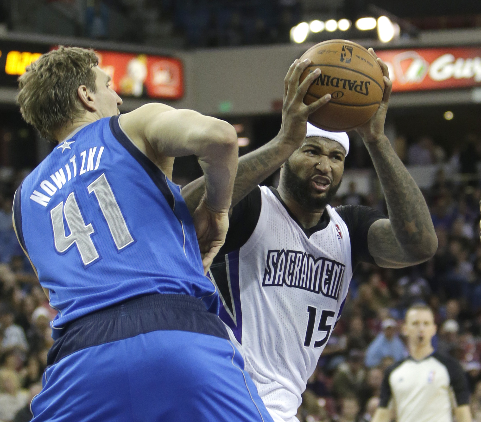 Sacramento Kings center DeMarcus Cousins, right, goes to the basket against Dallas Mavericks forward Dirk Nowitzki, of Germany, during the third quarter of an NBA basketball game in Sacramento, Calif., Monday, Dec. 9, 2013.  The Kings won 112-97