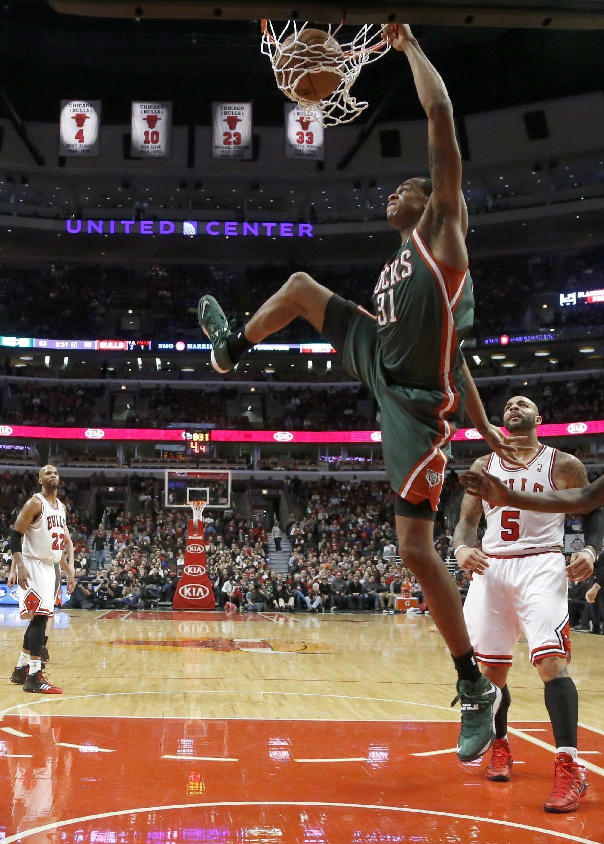 Milwaukee Bucks power forward John Henson (31) dunks the ball past Chicago Bulls power forward Carlos Boozer (5) during the second half of an NBA basketball game Tuesday, Dec. 10, 2013, in Chicago. The Bucks won 78-74