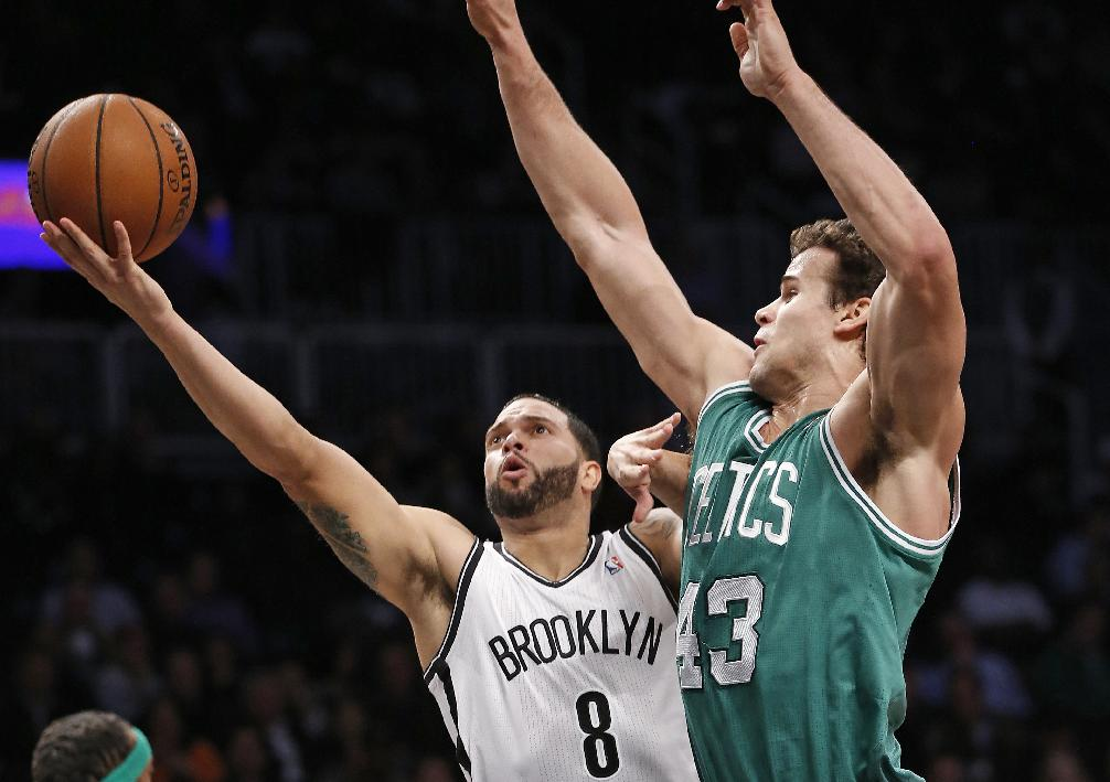 Brooklyn Nets guard Deron Williams (8) looks to shoot over the defense of Boston Celtics forward Kris Humphries (43) in the first half of their their NBA basketball game, Tuesday, Dec. 10, 2013, in New York. Williams, in his return from recurring ankle injuries, was the Nets high scorer with 25 points in the Nets 104-96 victory over the Boston Celtics