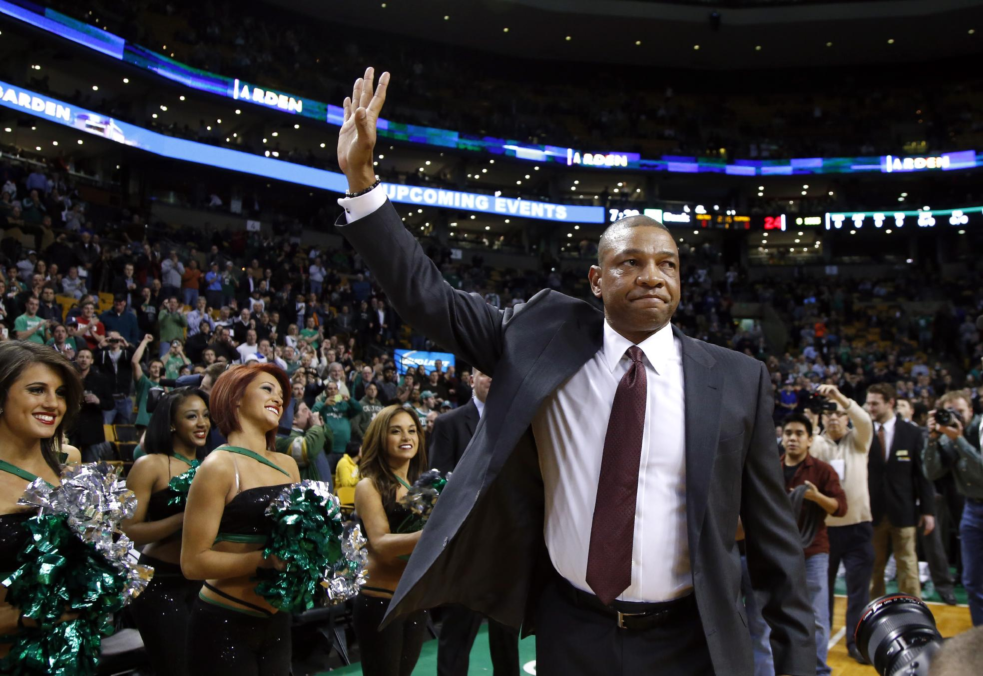 Doc Rivers, former head coach of the Boston Celtics and current head coach of the Los Angeles Clippers, waves to cheering fans as he enters the TD Garden floor for his first time back, before an NBA basketball game in Boston, Wednesday, Dec. 11, 2013