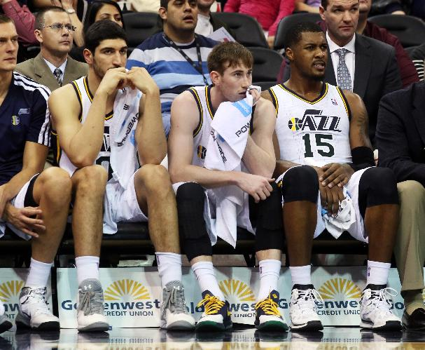 Utah Jazz's Enes Kanter, left, Utah Jazz's Gordon Hayward, middle, and Utah Jazz's Derrick Favors (15) sit on the bench late in the second half while trailing the San Antonio Spurs during an NBA basketball game on Saturday, Dec. 14, 2013, in Salt Lake City. San Antonio won the game 100-84