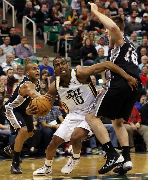 Utah Jazz's Alec Burks (10) drives the basket as San Antonio Spurs' guard Patty Mills, left, and San Antonio Spurs' Aron Baynes (16) defend in the second half of an NBA basketball game on Saturday, Dec. 14, 2013, in Salt Lake City. San Antonio won the game 100-84