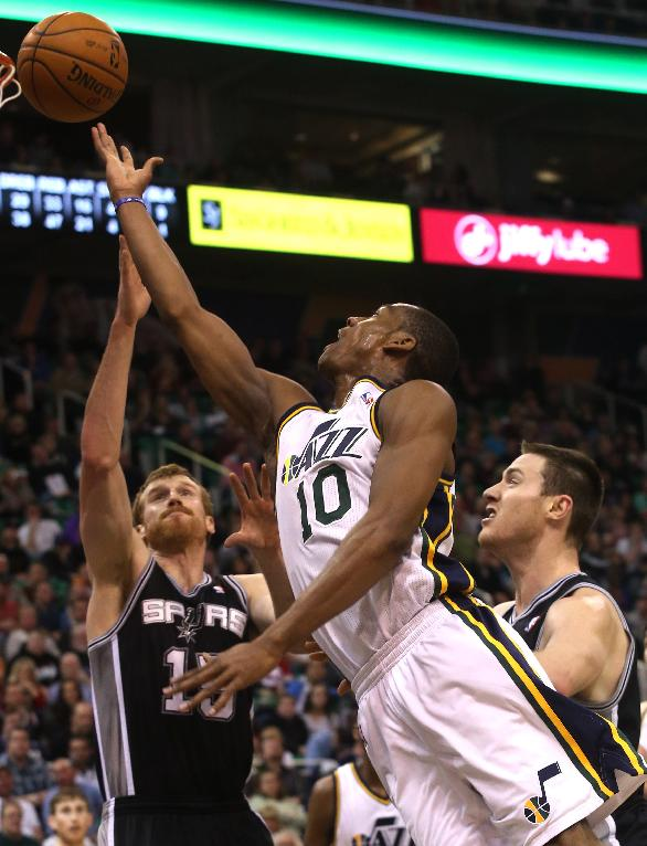Utah Jazz's Alec Burks (10) shoots the ball as San Antonio Spurs' Matt Bonner, left, and Aron Baynes, right, defend in the second half of an NBA basketball game on Saturday, Dec. 14, 2013, in Salt Lake City. San Antonio won the game 100-84
