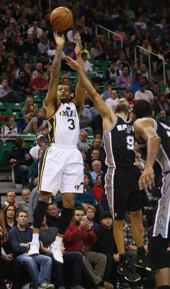 Utah Jazz's Trey Burke (3) takes a shot as San Antonio Spurs' guard Tony Parker (9) defends in the second half of an NBA basketball game on Saturday, Dec. 14, 2013, in Salt Lake City. San Antonio won the game 100-84