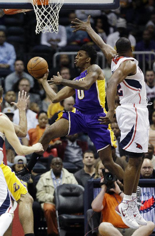 Los Angeles Lakers forward Nick Young (0) scores against Atlanta Hawks' Al Horford in the first half of an NBA basketball game, Monday, Dec. 16, 2013, in Atlanta