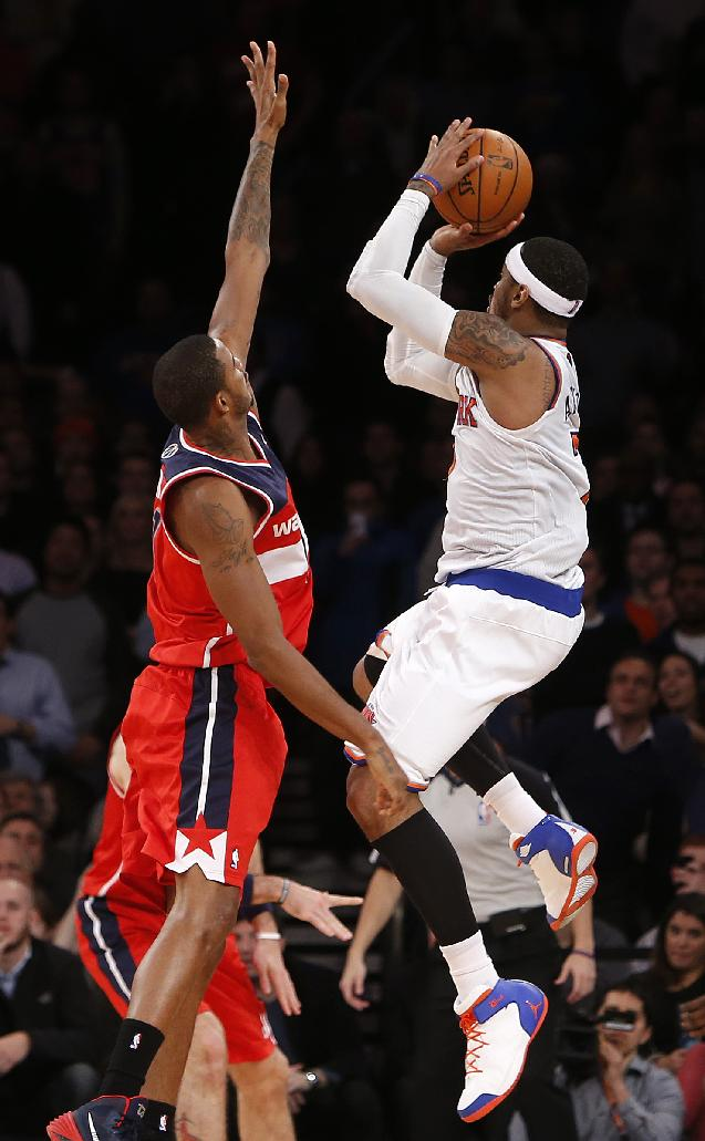 New York Knicks' Carmelo Anthony, right, misses the potential game-winning shot against Washington Wizards' Trevor Ariza in the final seconds of the second half of an NBA basketball game Monday, Dec. 16, 2013, in New York.  The Wizards won 102-101
