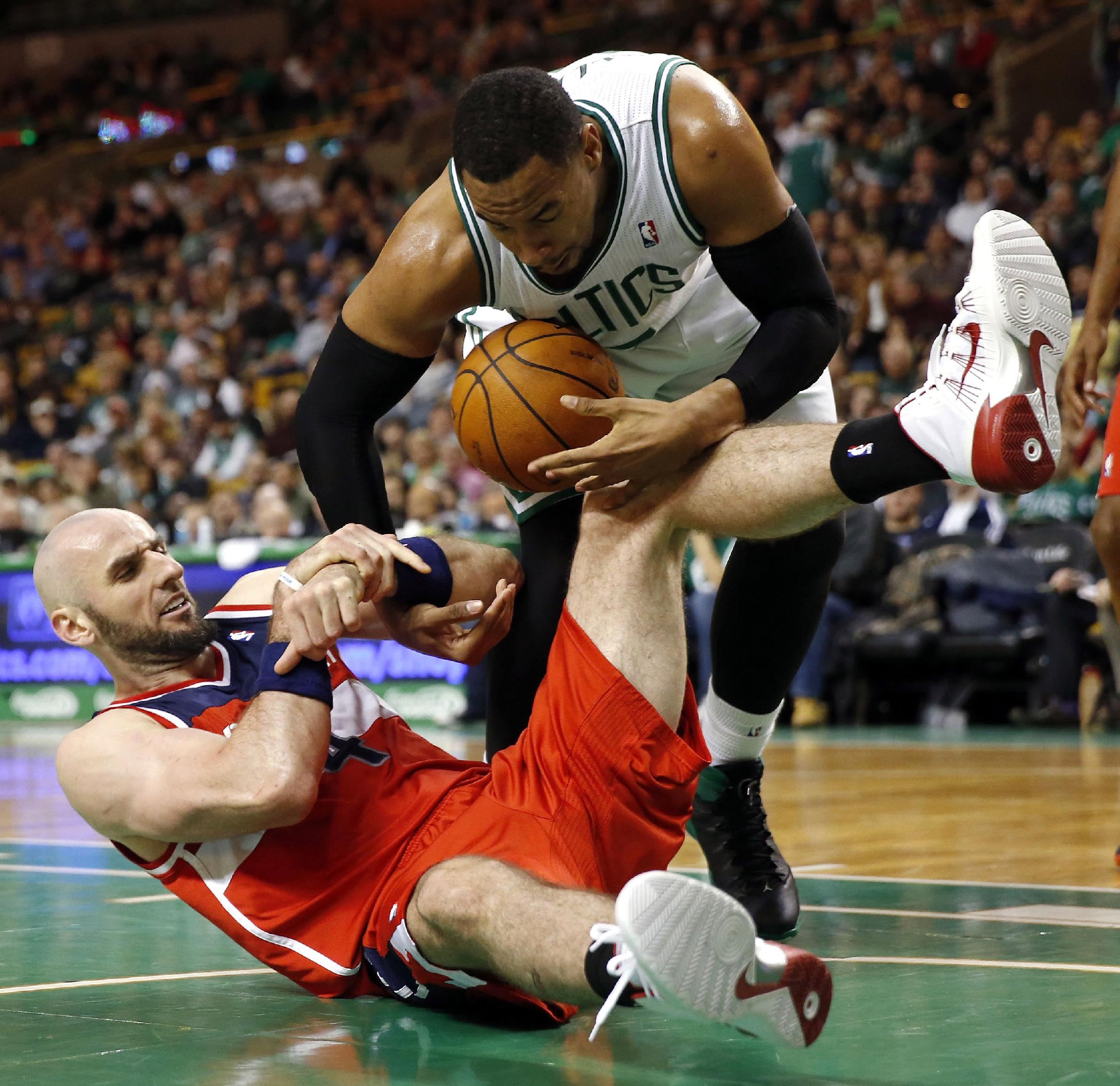 Boston Celtics' Jared Sullinger (7) and Washington Wizards' Marcin Gortat (4) battle for a loose ball in the third quarter of an NBA basketball game in Boston, Saturday, Dec. 21, 2013. The Wizards won 106-99