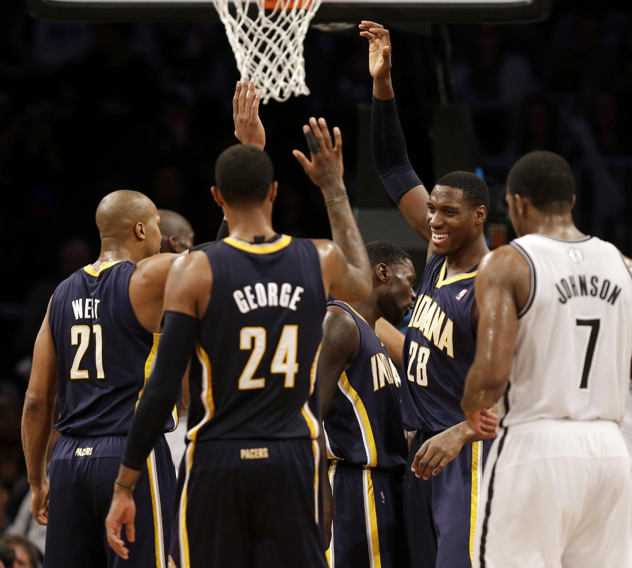 While Brooklyn Nets' Joe Johnson (7) watches, Indiana Pacers' David West (21), lPaul George (24) and Ian Mahinmi (28) celebrate with teammates during the second half of an NBA basketball game Monday, Dec. 23, 2013, in New York. The Pacers defeated the Nets 103-86