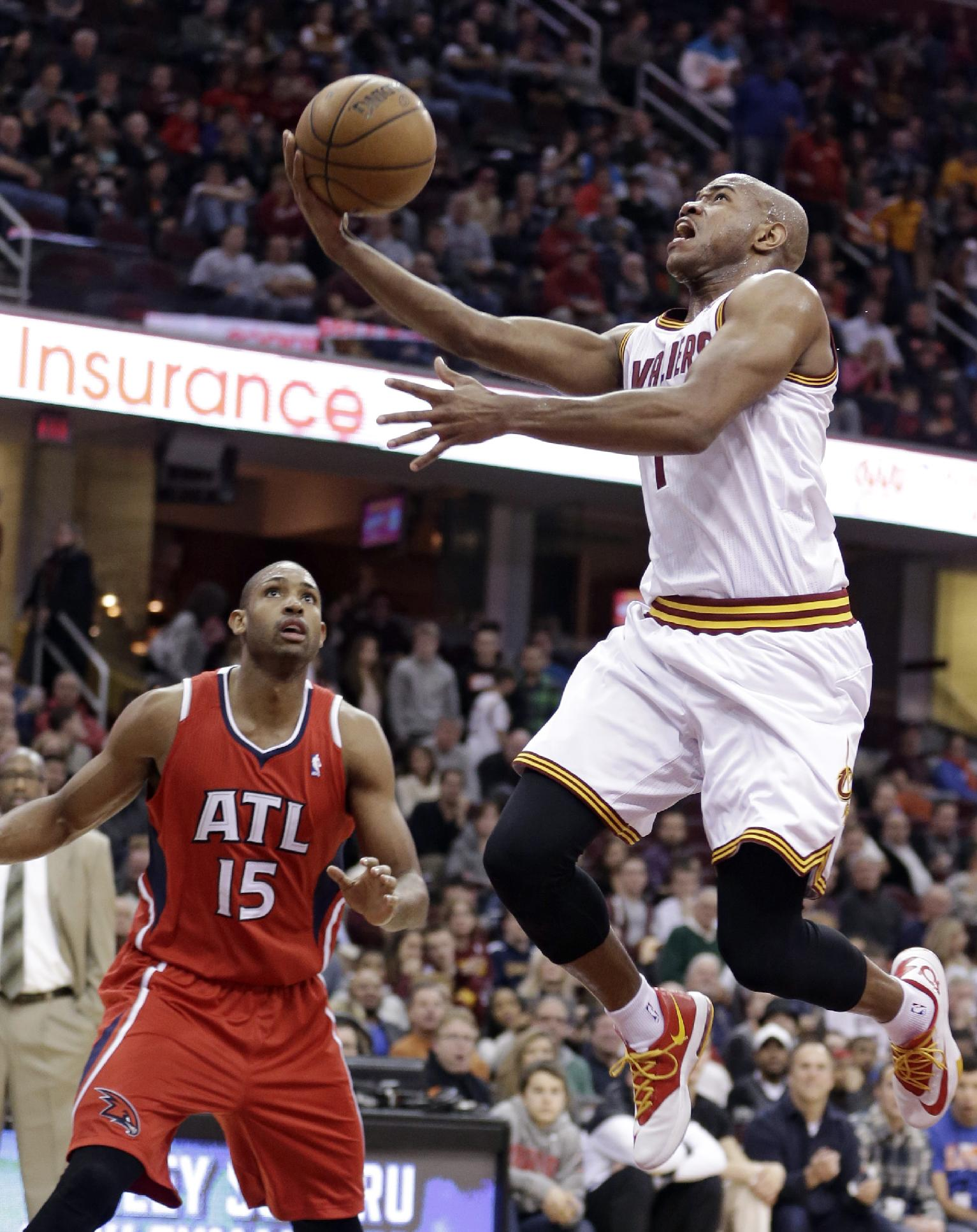 Cleveland Cavaliers' Jarrett Jack (1) jumps to the basket against Atlanta Hawks' Al Horford (15) during the second quarter of an NBA basketball game Thursday, Dec. 26, 2013, in Cleveland