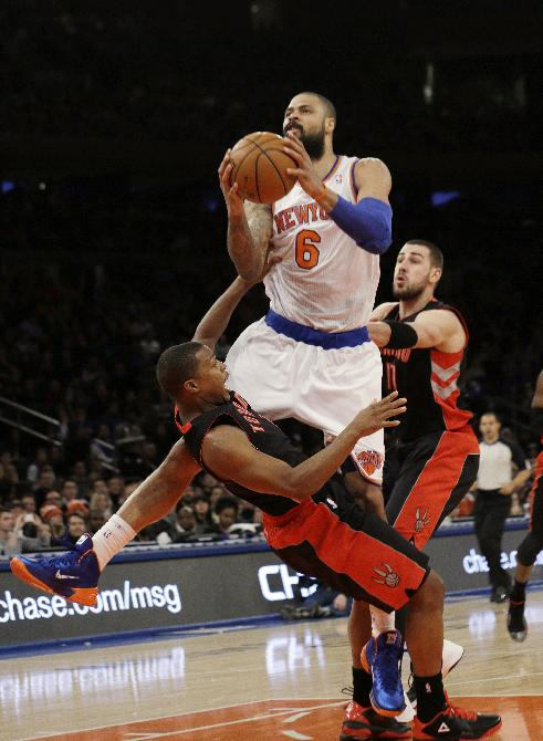 New York Knicks' Tyson Chandler (6) drives past Toronto Raptors' Kyle Lowry, front, during the first half of an NBA basketball game Friday, Dec. 27, 2013, in New York. Chandler was called for a foul on the play