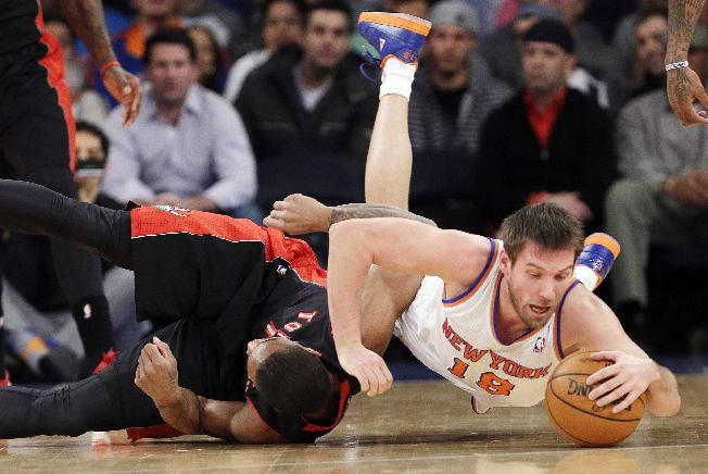 New York Knicks' Beno Udrih (18), of Slovenia, dives past Toronto Raptors' DeMar DeRozan during the first half of an NBA basketball game Friday, Dec. 27, 2013, in New York
