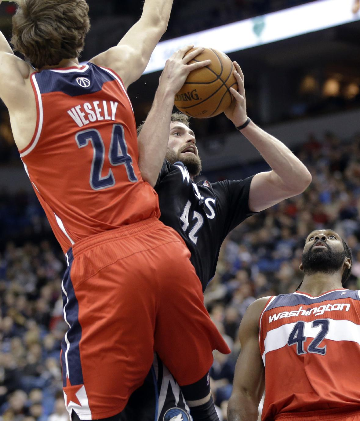 Minnesota Timberwolves' Kevin Love lays up a shot between Washington Wizards' Jan Vesely, left, of the Czech Republic, and Nene Hilario, of Brazil, during the first quarter of an NBA basketball game, Friday, Dec. 27, 2013, in Minneapolis