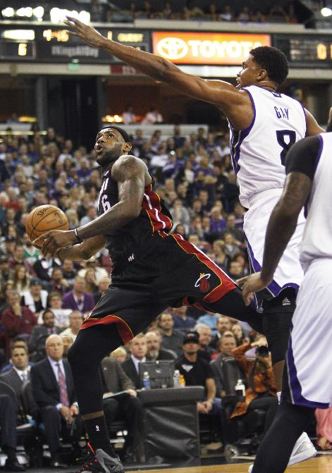 Miami Heat forward LeBron James (6) puts up a shot against Sacramento Kings defender Rudy Gay (8) during the first half of an NBA basketball game on Friday, Dec. 27, 2013, in Sacramento, Calif