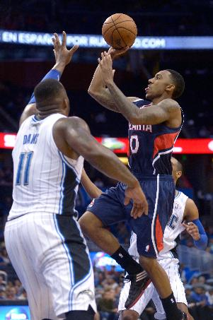 Atlanta Hawks guard Jeff Teague (0) goes up for a shot in front of Orlando Magic forward Glen Davis (11) during the first half of an NBA basketball game in Orlando, Fla., Sunday, Dec. 29, 2013