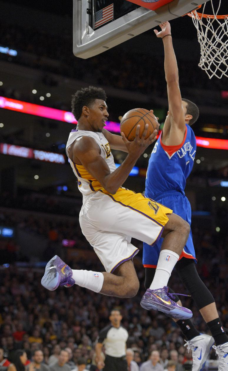 Los Angeles Lakers forward Nick Young, left, puts up a shot as Philadelphia 76ers guard Michael Carter-Williams defends during the first half of an NBA basketball game, Sunday, Dec. 29, 2013, in Los Angeles