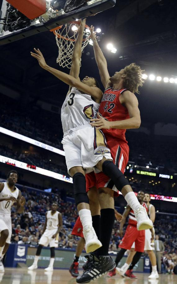 New Orleans Pelicans forward Anthony Davis (23) goes to the basket as Portland Trail Blazers center Robin Lopez (42) tries to block in the first half of an NBA basketball game in New Orleans, Monday, Dec. 30, 2013