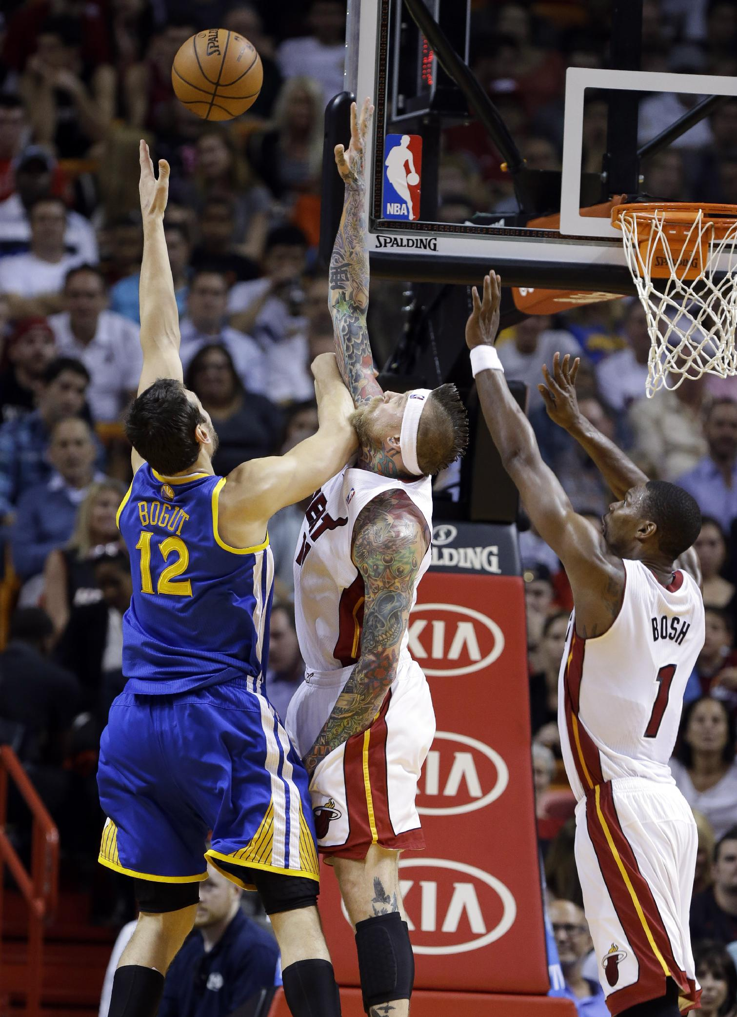 Golden State Warriors' Andrew Bogut (12) shoots as Miami Heat's Chris Andersen, center, and Chris Bosh (1) defend during the first half of an NBA basketball game, Thursday, Jan. 2, 2014, in Miami