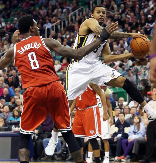 Utah Jazz's Trey Burke, right, passes the ball past Milwaukee Bucks' Larry Sanders (8) during the second half of an NBA basketball game Thursday, Jan. 2, 2014, in Salt Lake City. The Jazz won 96-87
