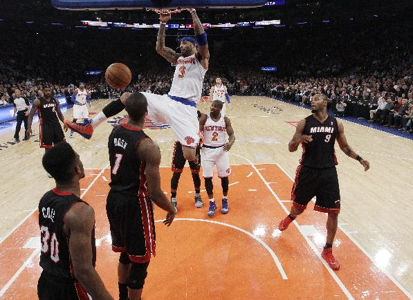 New York Knicks' Kenyon Martin (3) holds onto the rim after dunking the ball in front of Miami Heat's Chris Bosh (1) and Norris Cole (30) during the first half of an NBA basketball game on Thursday, Jan. 9, 2014, in New York