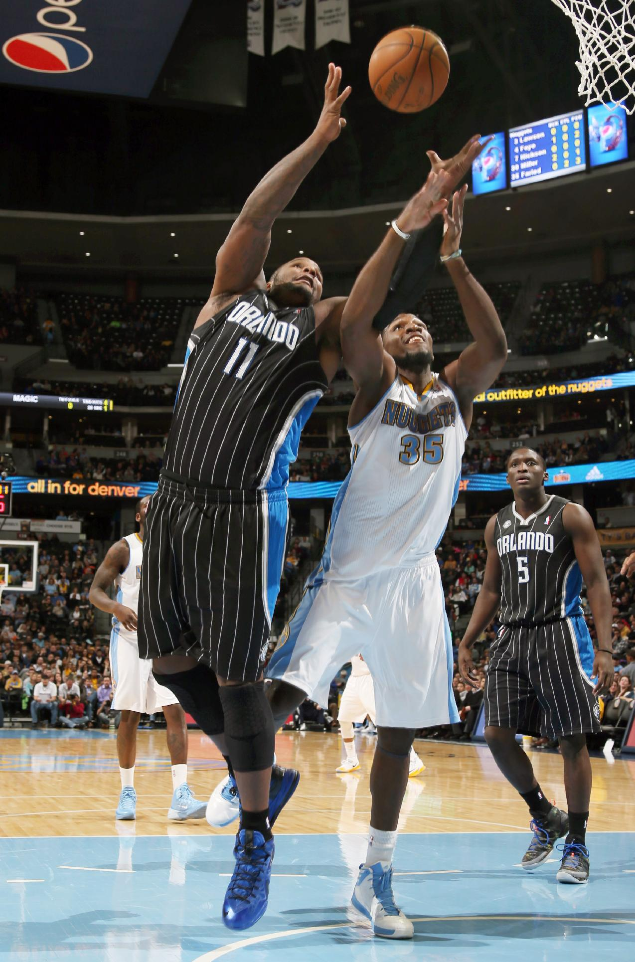 Orlando Magic center Glen Davis, left, battles for control of a rebound with Denver Nuggets forward Kenneth Faried in the third quarter of the Nuggets' 120-94 victory in an NBA basketball game in Denver on Saturday, Jan. 11, 2014
