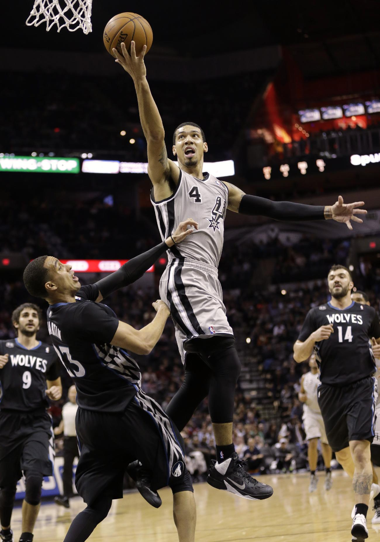 San Antonio Spurs' Danny Green (4) shoots over Minnesota Timberwolves' Kevin Martin (23) during the first half on an NBA basketball game, Sunday, Jan. 12, 2014, in San Antonio