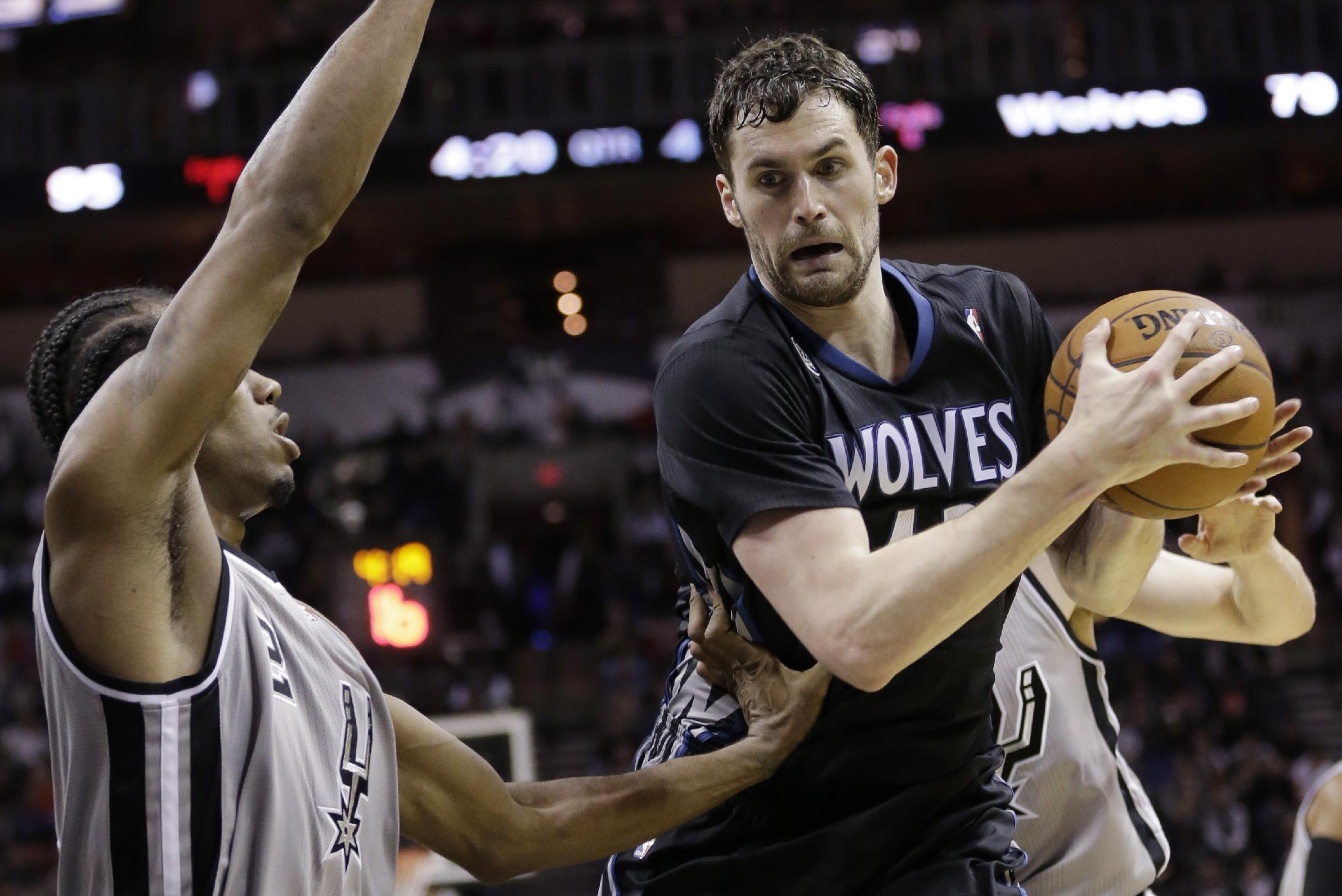 Minnesota Timberwolves' Kevin Love, right, is pressured by San Antonio Spurs' Kawhi Leonard, left, during the second half on an NBA basketball game, Sunday, Jan. 12, 2014, in San Antonio. San Antonio won 104-86