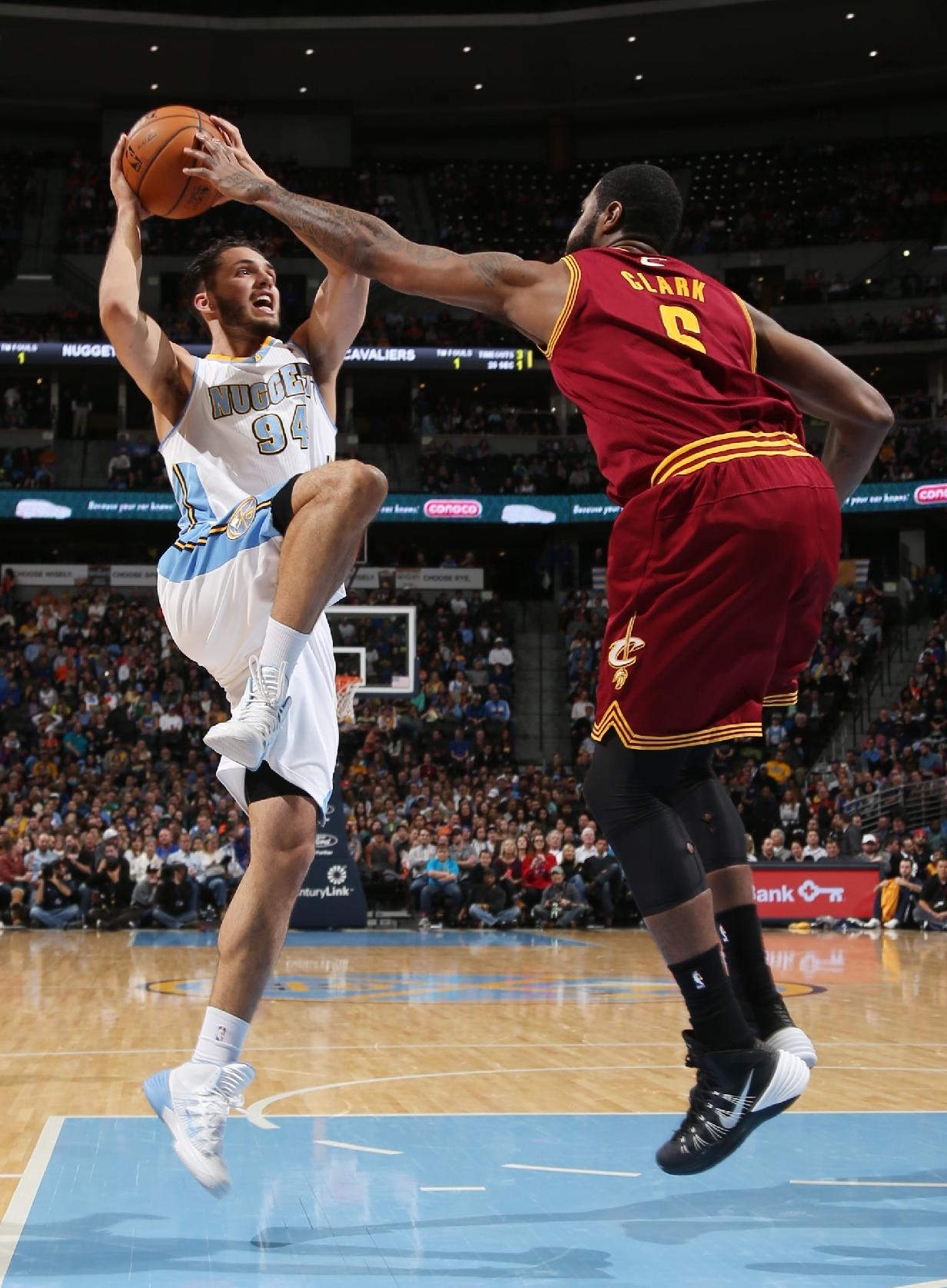 Denver Nuggets guard Evan Fournier, left, of France, his his shot blocked by Cleveland Cavaliers forward Earl Clark in the fourth quarter of the Cavaliers' 117-109 victory in an NBA basketball game in Denver on Friday, Jan. 17, 2014