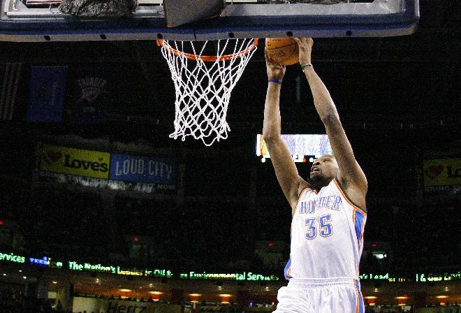 Oklahoma City Thunder small forward Kevin Durant (35) goes up for a dunk against the Golden State Warriors during the first half of an NBA basketball game Friday, Jan. 17, 2014, in Oklahoma City