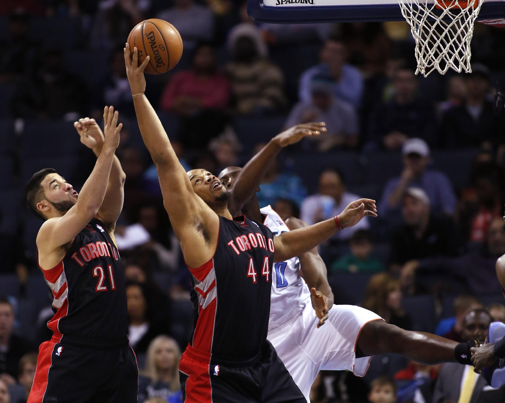 Toronto Raptors guard Greivis Vasquez, of Venezuela (21). and forward Chuck Hayes (44) battle Charlotte Bobcats center Bismack Biyombo, of the Democratic Republic of Congo, for a rebound in the first half of an NBA basketball game Monday, Jan. 20, 2014 in Charlotte, N.C