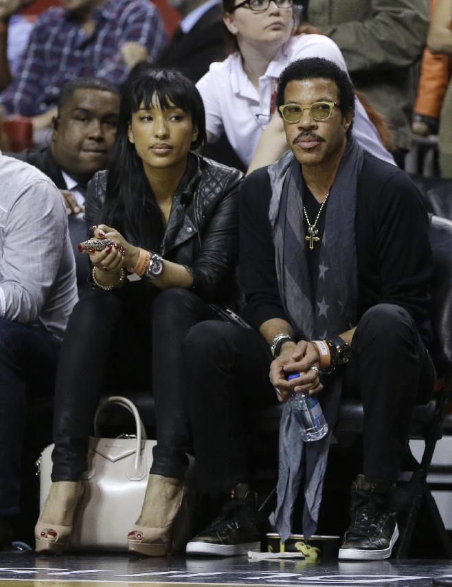 Singer-songwriter Lionel Richie, right, watches the Boston Celtics play against the Miami Heat during an NBA basketball game in Miami, Tuesday, Jan. 21, 2014